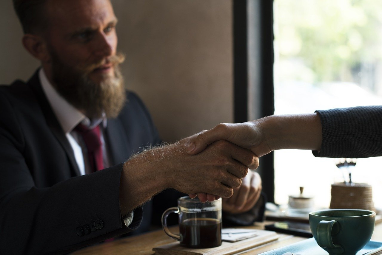 Win a suit - bearded man shaking another man's hand across a desk