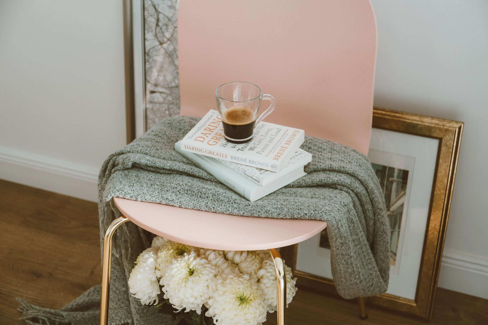 Beck Valley Books - grey throw on a pink chair with a stack of books and coffee cup on top