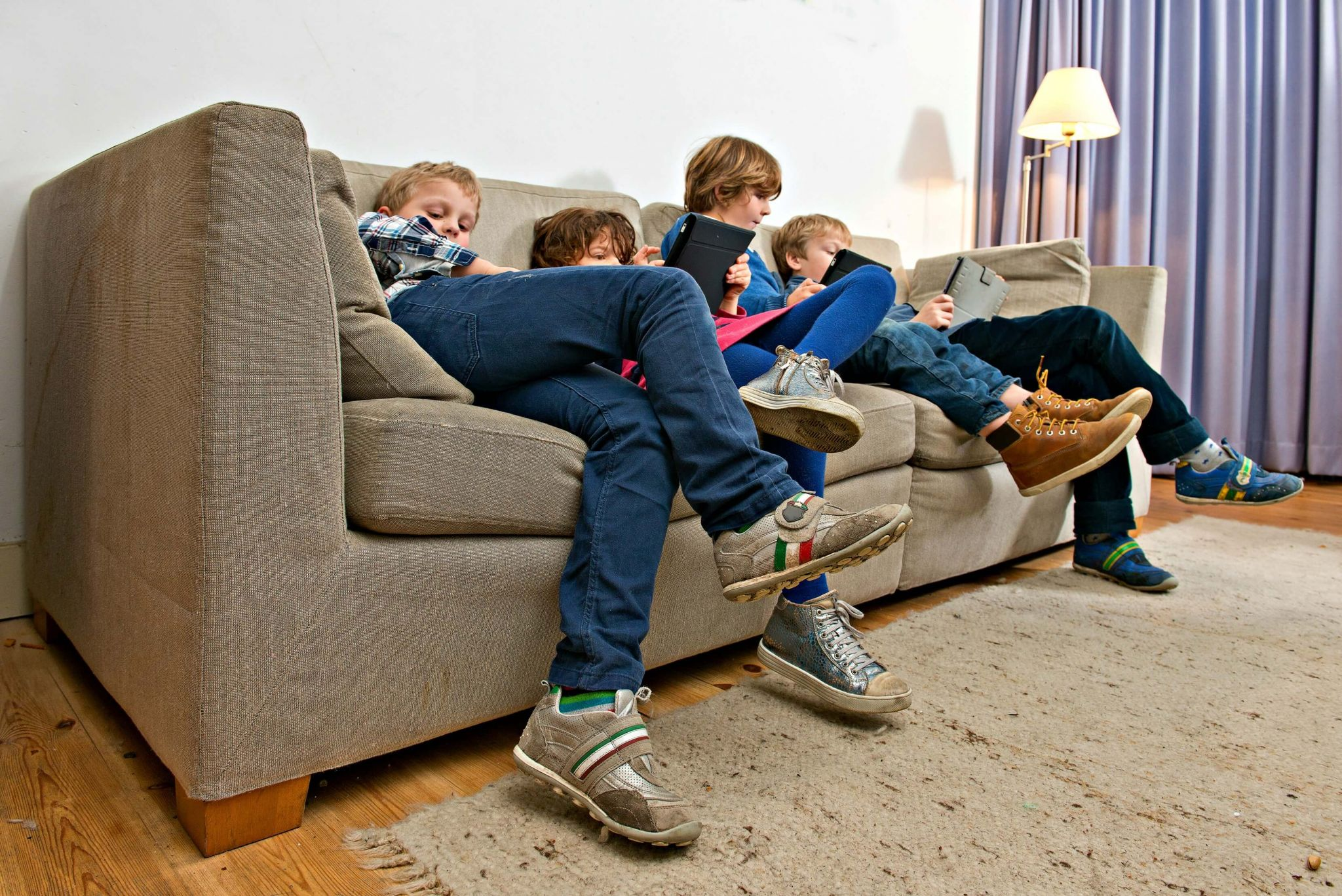 dangers of online gaming - four children slumped on a sofa playing with iPads