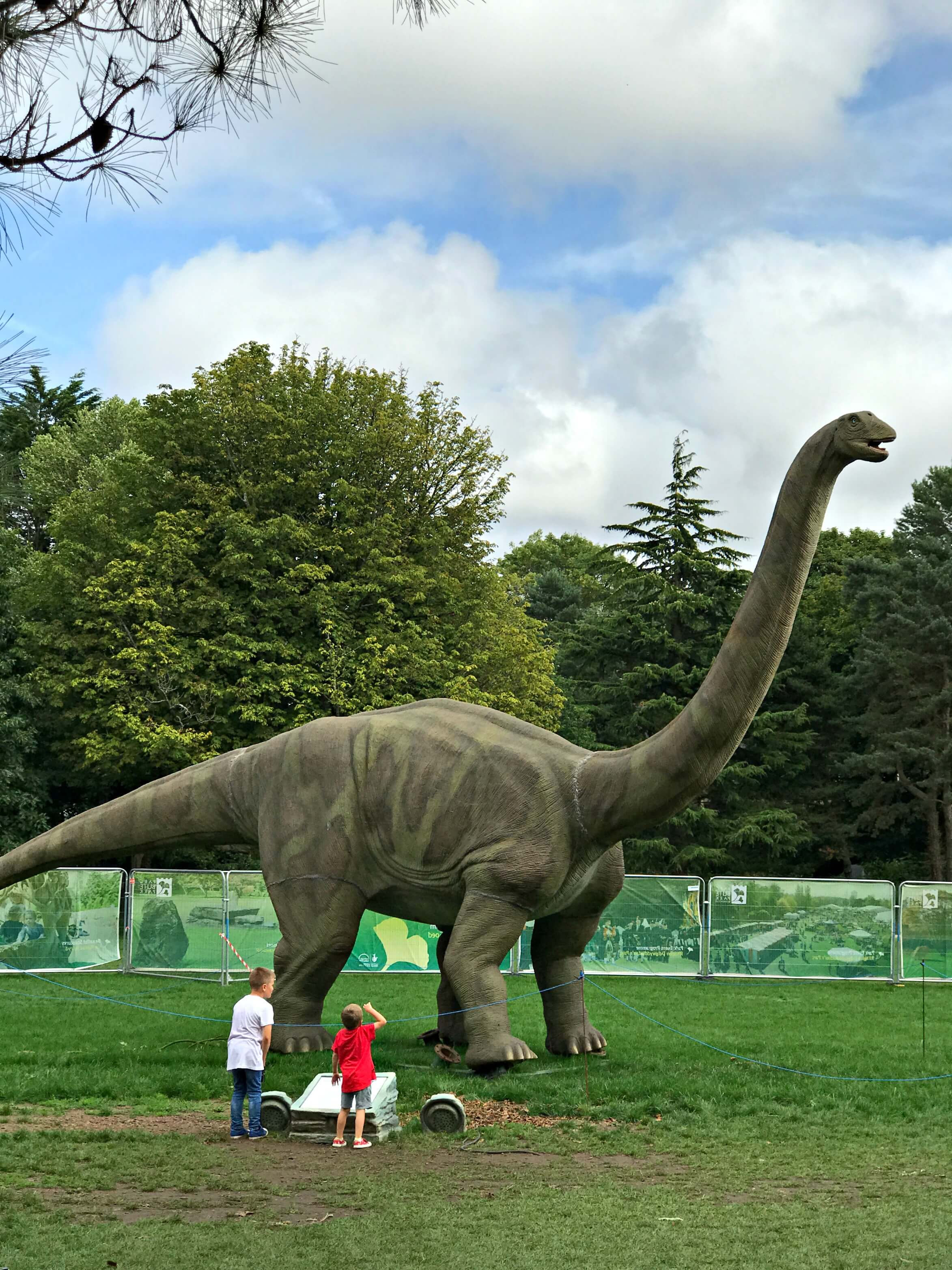 Jurassic Kingdom - 2 kids in front of a brontosaurus