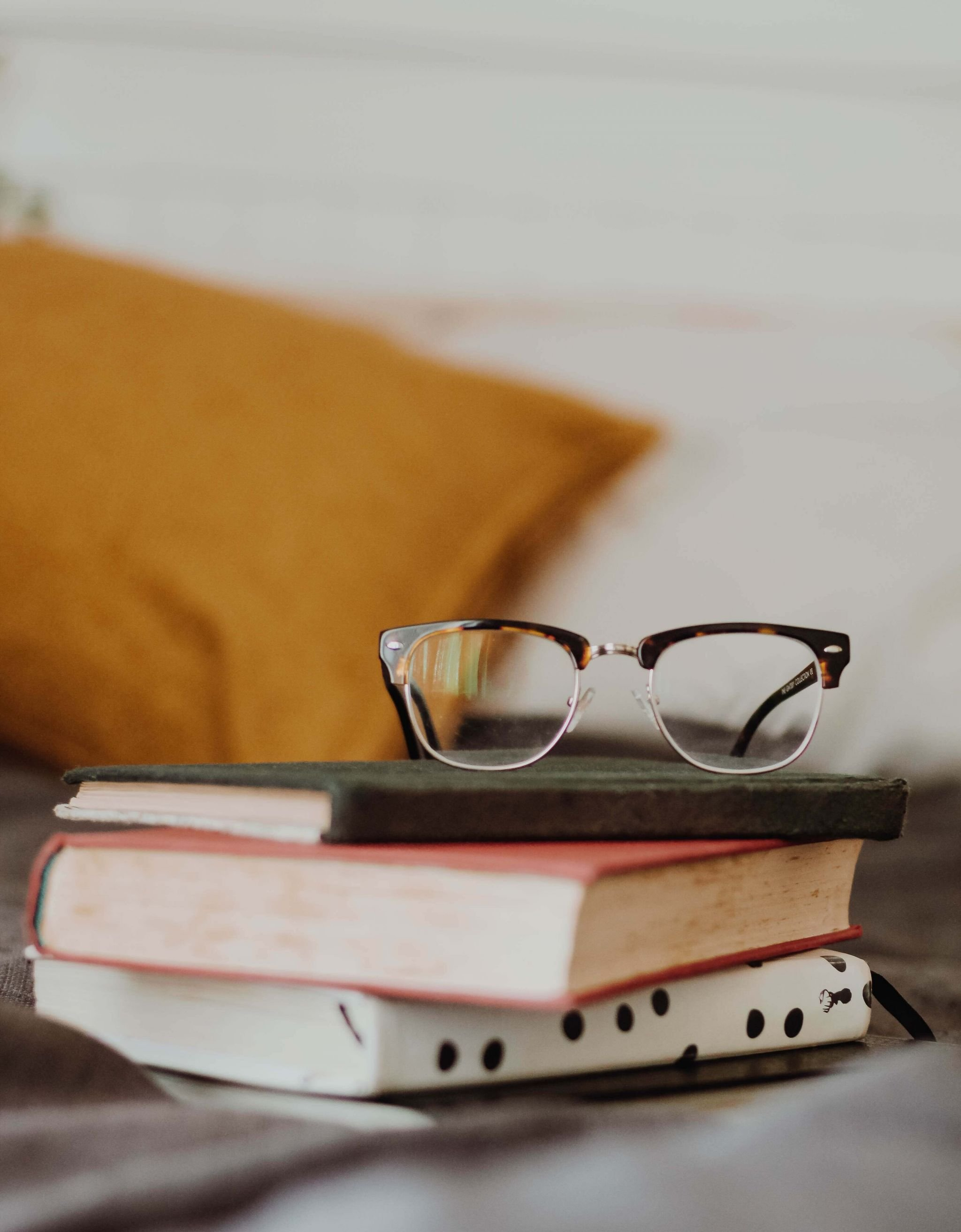 free and bargain books - yellow cushion, stack of books and a woman's glasses