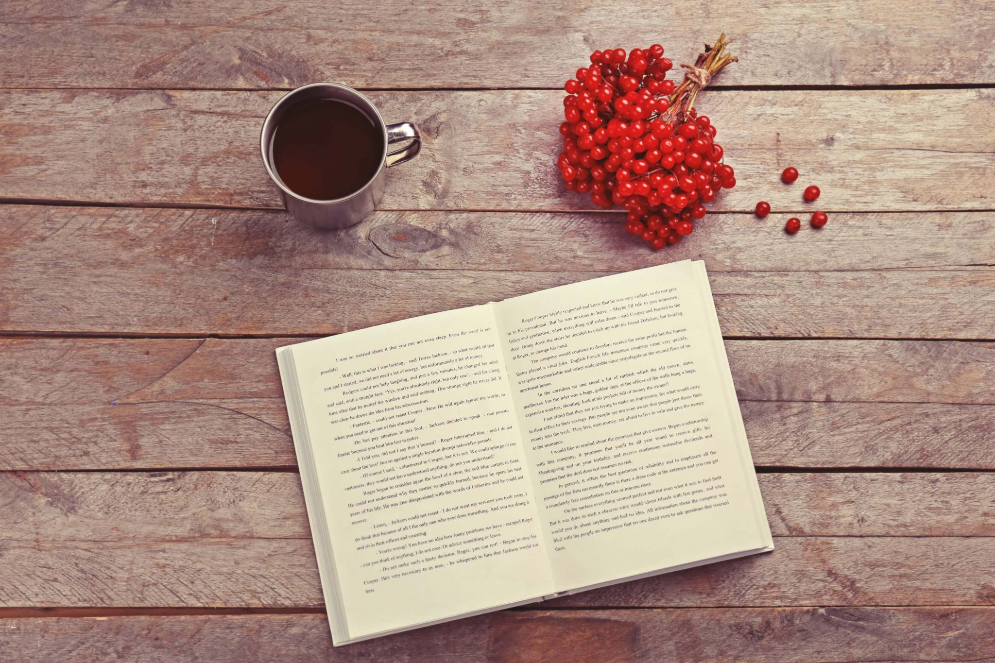 free and bargain books - silver coffee cup, red berries and open book on a wooden floor