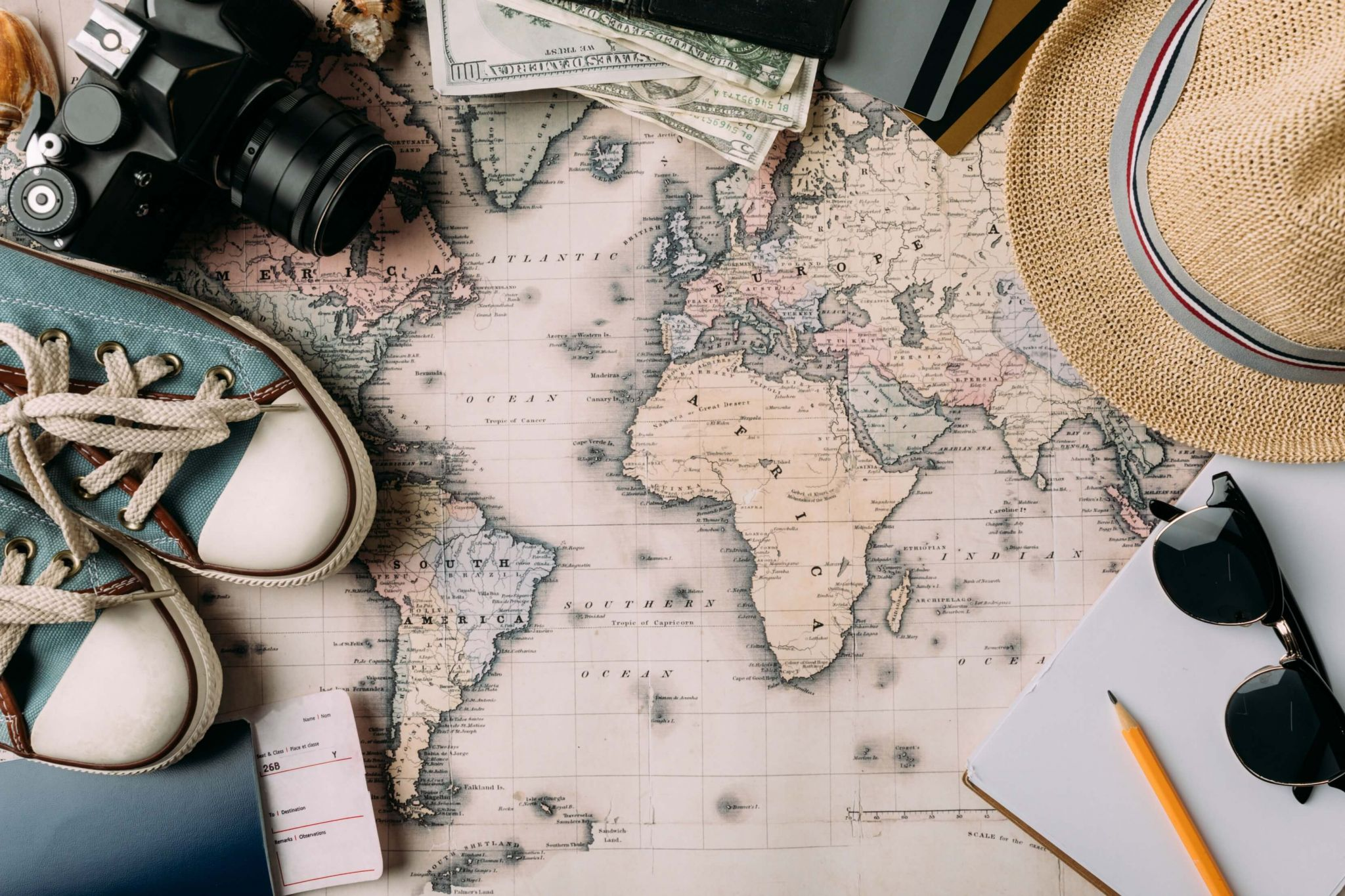 travel insurance with pre existing medical conditions - map of the world with hat, binoculars, sunglasses and trainers