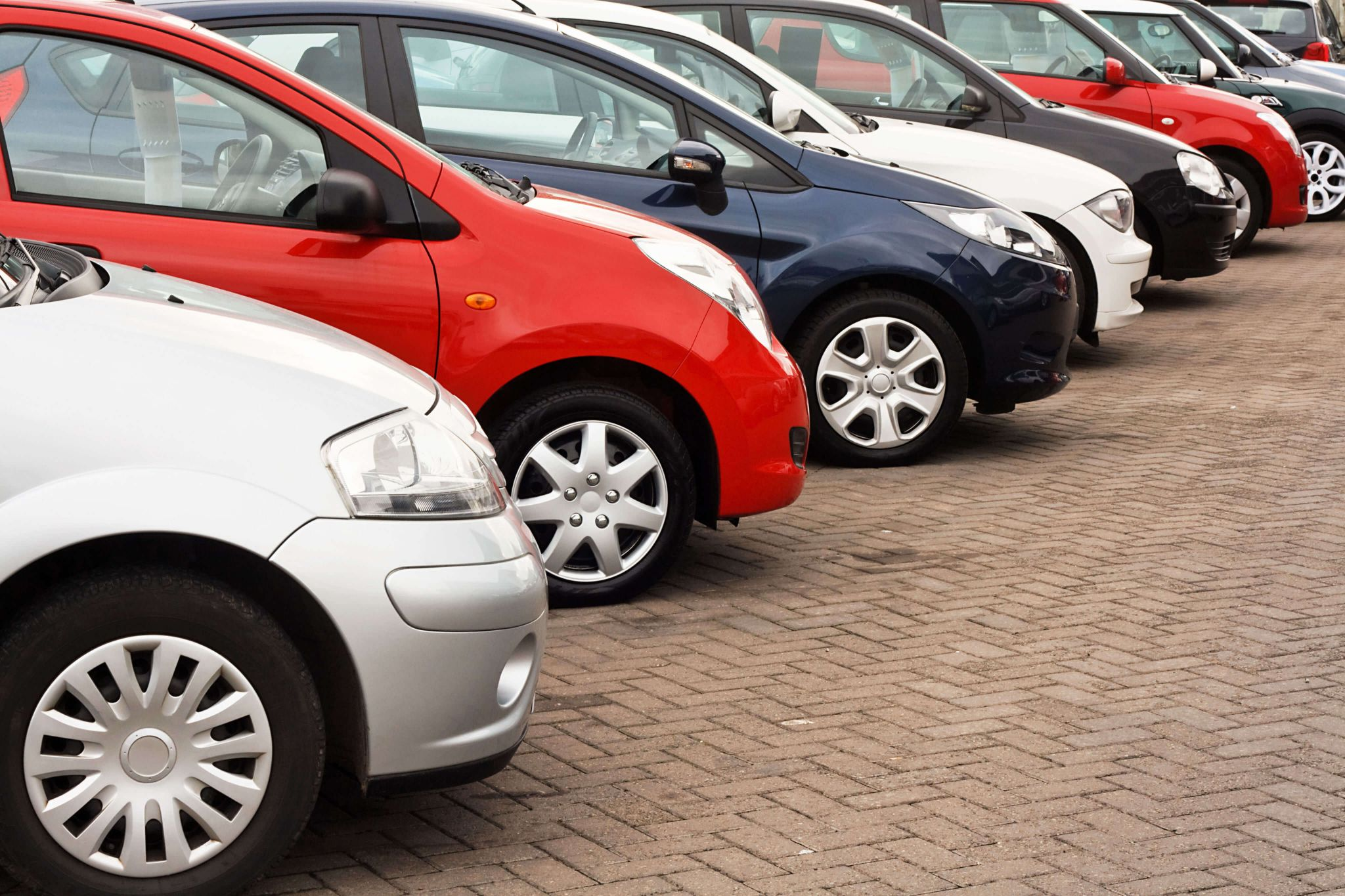 financing your first car - line of family cars on a garage forecourt