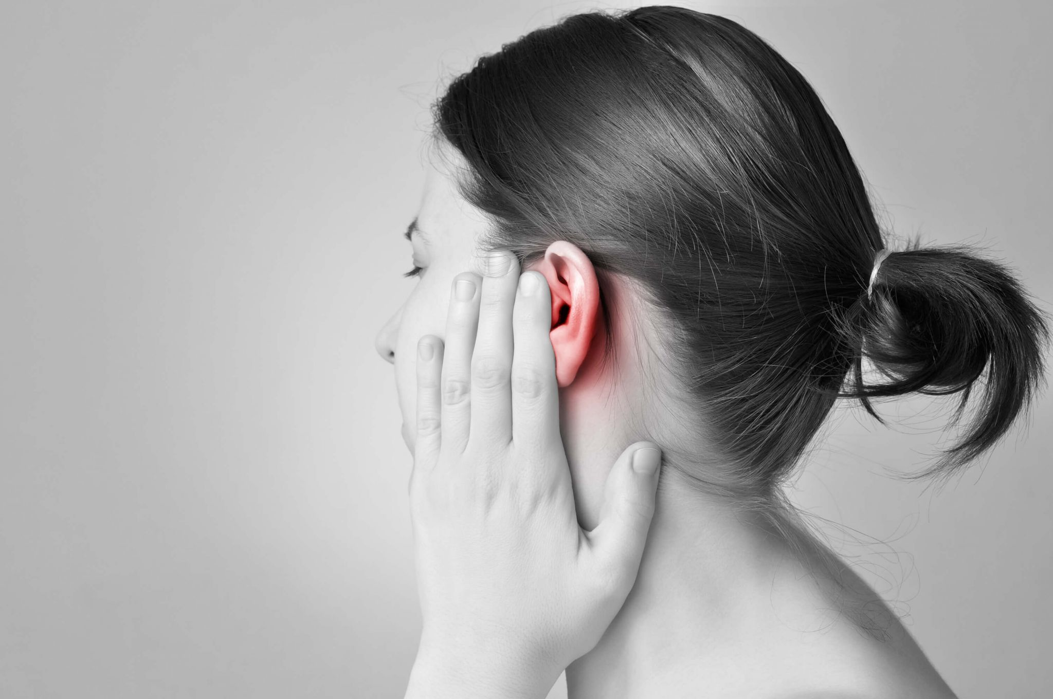 common ear problems - woman holding her aching ear