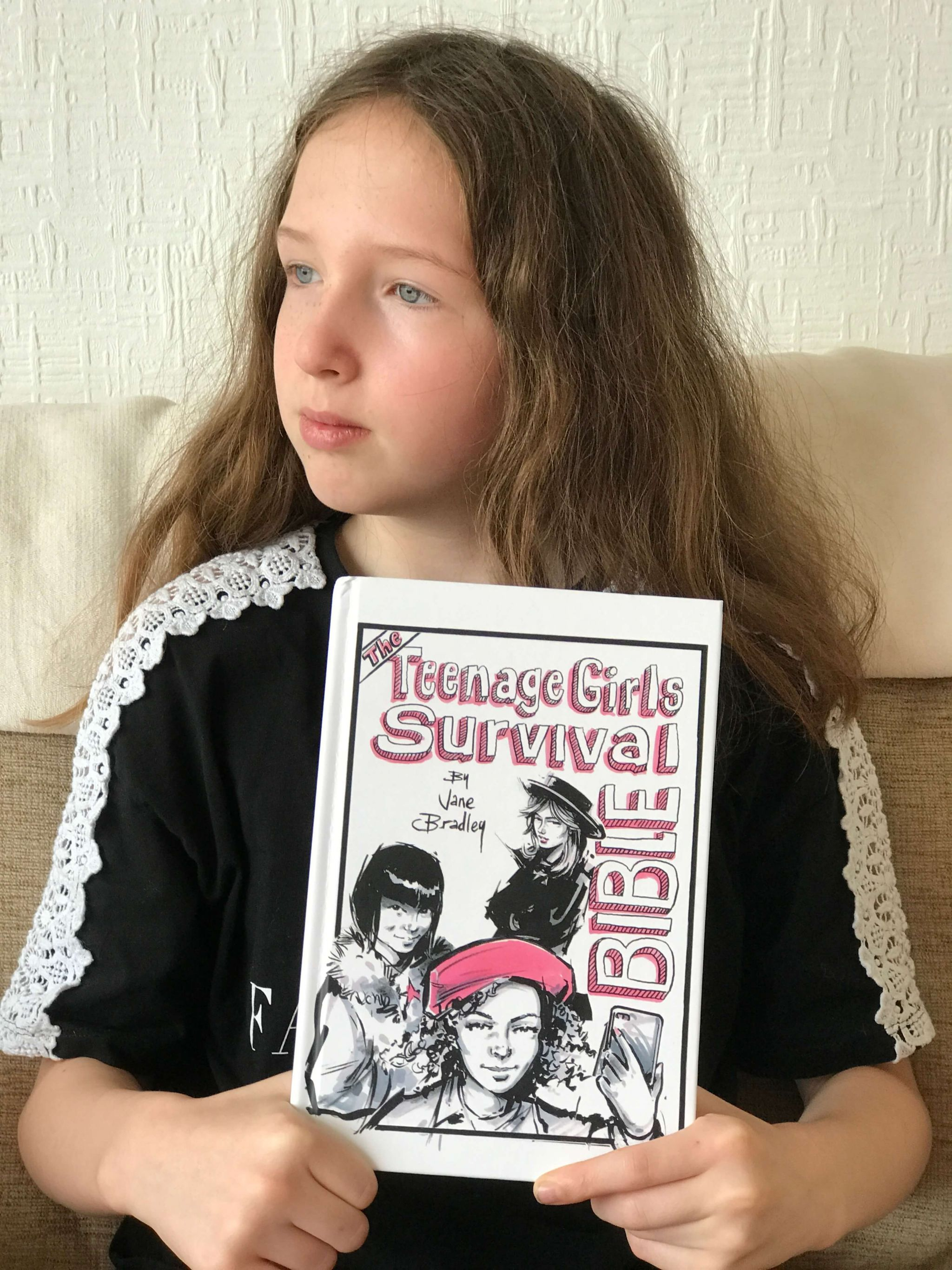 teenage girls issues - Caitlin holding The Teenage Girls Survival Bible book