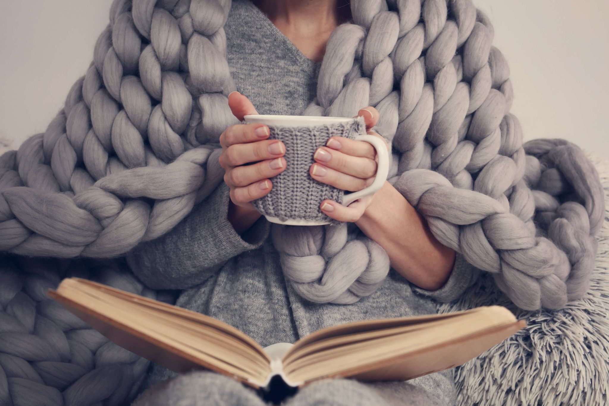 winter home improvements - woman wrapped in a grey blanket clutching a white mug with a grey knitted cosy