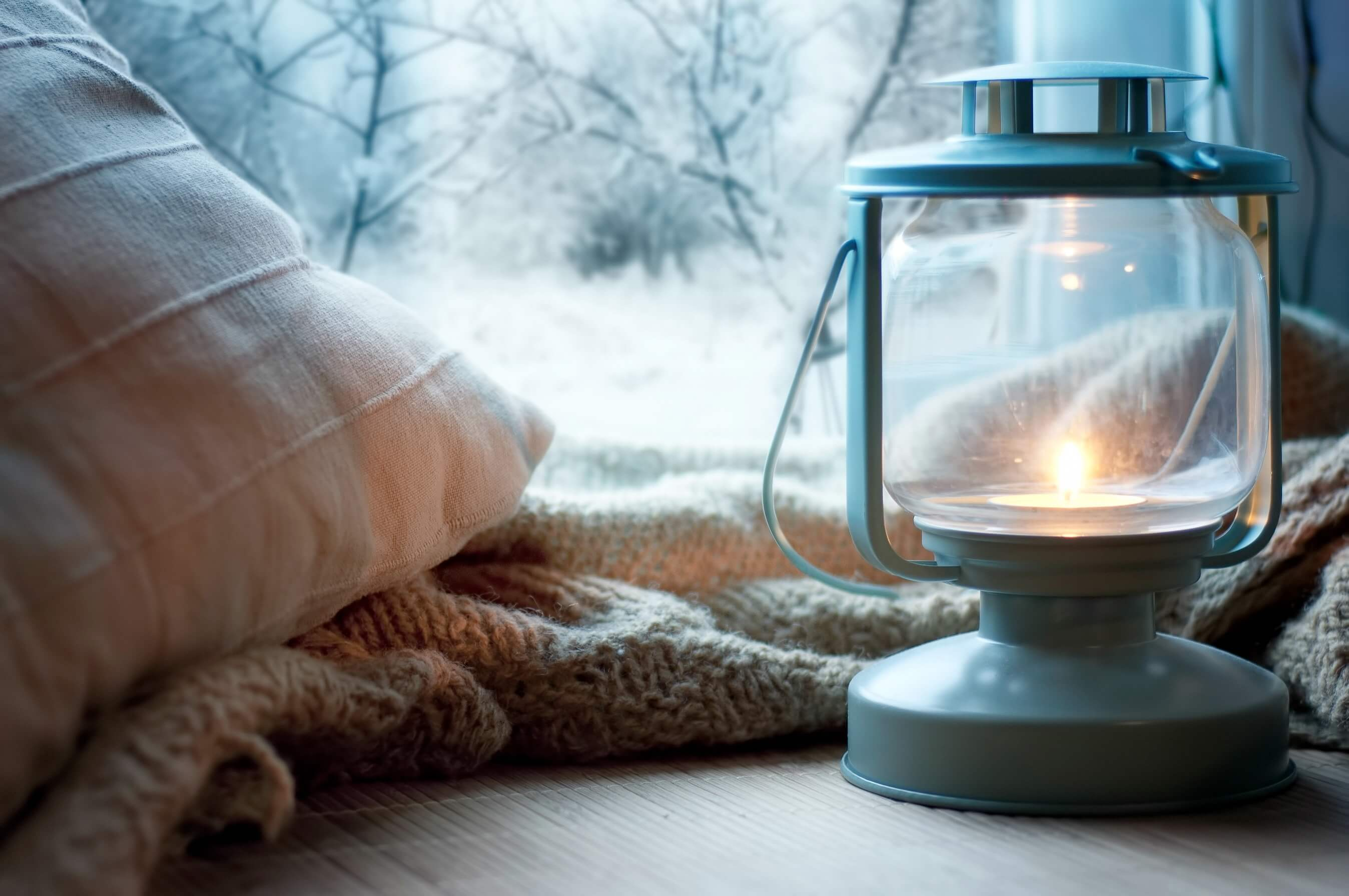 Get your home ready for winter - snowy scene with lantern and throw