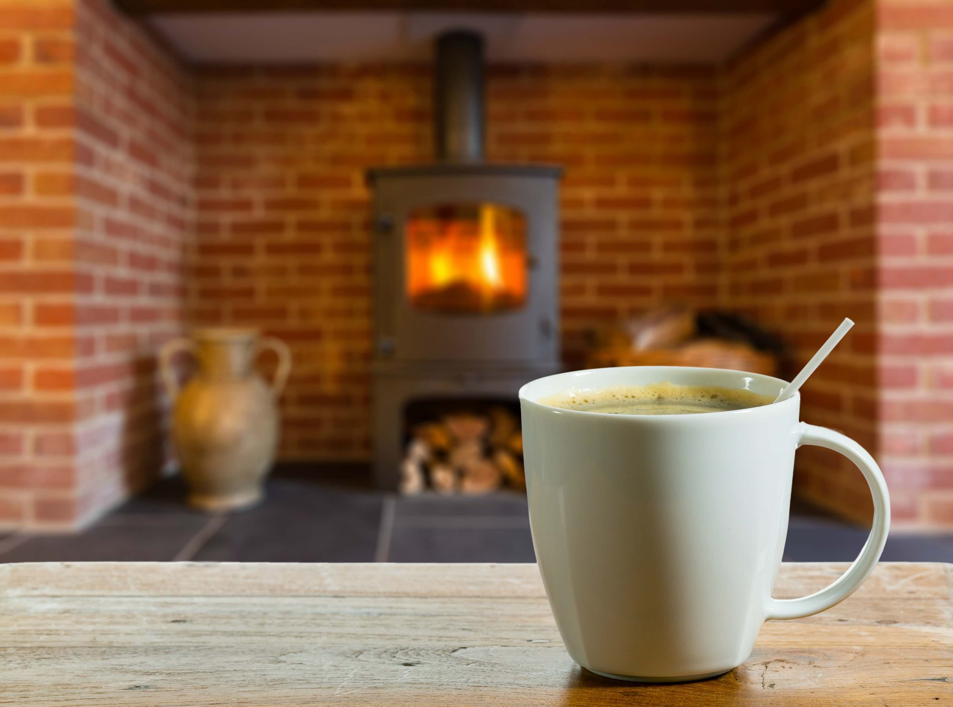 get your home ready for winter - mug of hot chocolate in front of a wood burning stove
