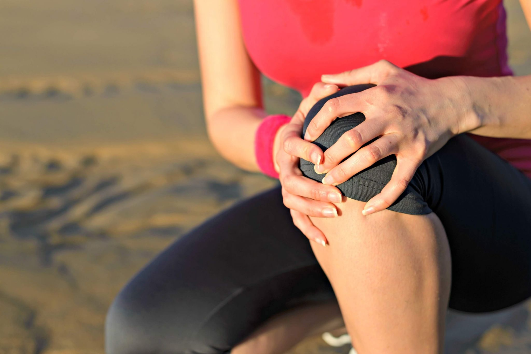 joint pain - woman runner holding her knee